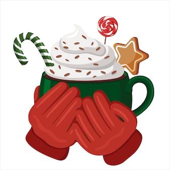 赤い手袋をした手は、ホットココア、ホイップクリーム、キャンディーで満たされた緑のカップを持っています。クリスマスの飲み物。