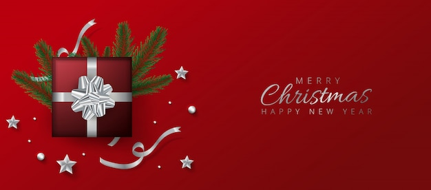 Red header or banner design decorated with gift box, baubles and pine leaves for merry christmas and happy new year.