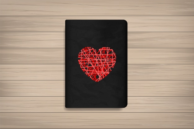 Red heart on book cover with wood background.