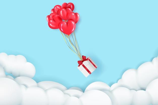 赤いハートの風船は、バレンタインデーのための弓の付いたギフトボックスを雲の中に運びます