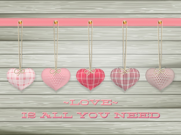 Red hearts hanging over old wood background.