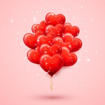 ピンクで分離されたハートの形の赤いヘリウム気球
