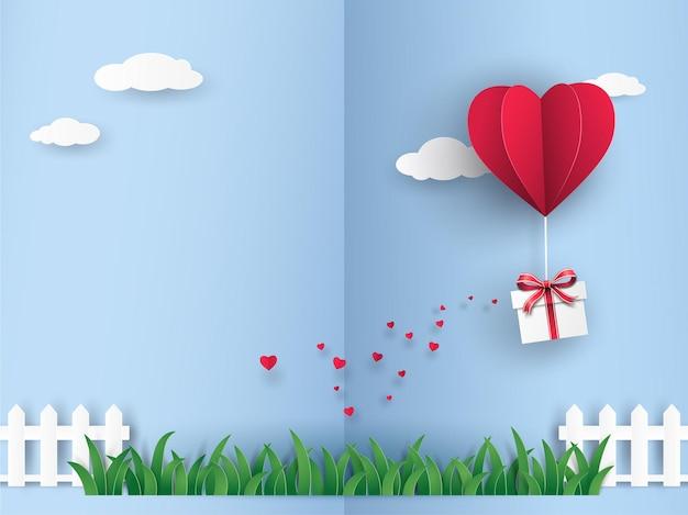 Красный оригами воздушный шар в форме сердца с подарочной коробкой, летящей по небу над зеленым лугом.