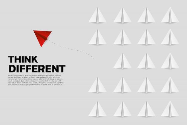 Красный оригами бумажный самолетик выходит из группы белых