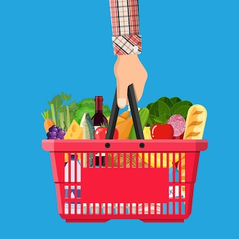 Red plastic shopping basket full of groceries products in hand