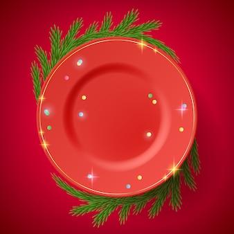 枝で飾られたテーブルの上の赤いプレート