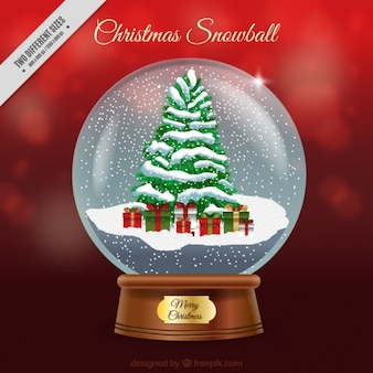Red unfocused background with christmas ball and snowy tree