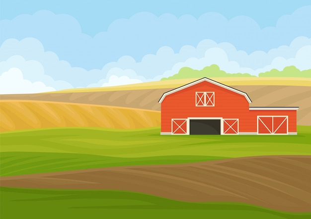 Red wooden shed with garage in a plowed field.