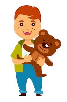 Redhead boy with freckles holds soft teddy bear