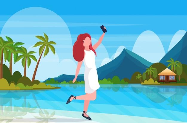 Рыжая женщина на пляже, принимая селфи фото на смартфон камеры летние каникулы концепция женщина мультипликационный персонаж позирует тропический остров приморский фон полная длина горизонтальный