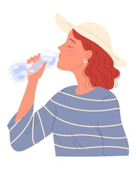 Redheaded girl with freckles and a hat drinking water from bottle.