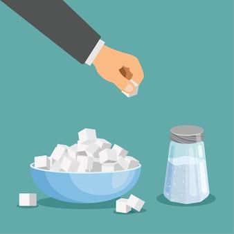 Рафинированный и рассыпной сахар в миске рука берет кубик сахара