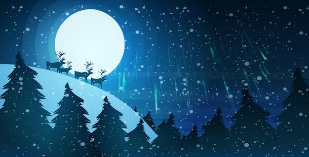 夜空に満月の上のトナカイのシルエット雪に覆われた松のモミの木の森のメリークリスマス新年あけましておめでとうございます冬の休日の概念