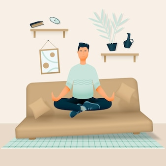 A relaxed smiling man sits in his room or apartment on a soft sofa with his legs crossed and meditates.