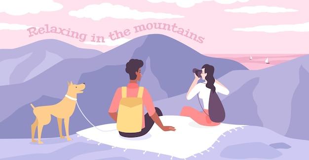 若いカップルと彼らの犬が山頂に座って双眼鏡で周りを見回しながら、平らな山でリラックスする