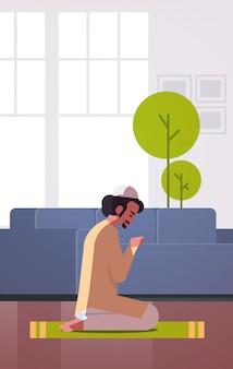 Религиозный мусульманин на коленях и молиться на ковер у себя дома
