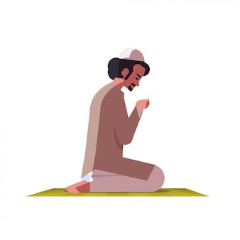 Религиозный мусульманин на коленях и молиться на ковер рамадан карим священный месяц религия концепция квартира полная длина