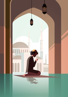 Religious muslim man kneeling on carpet and praying inside mosque ramadan kareem holy month religion concept full length vertical