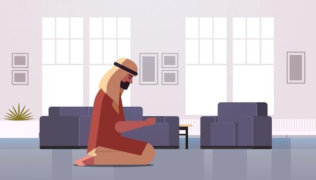 Religious muslim man kneeling and praying at home ramadan kareem holy month religion concept modern living room interior full length horizontal
