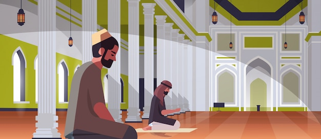 Religious muslim men couple kneeling and praying inside nabawi mosque building ramadan kareem holy month religion concept full length horizontal