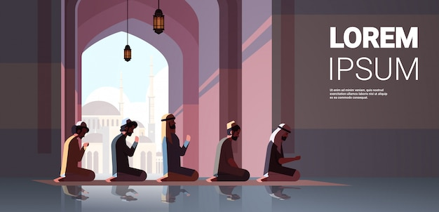 Religious muslim men kneeling and praying inside mosque ramadan kareem holy month religion concept full length copy space horizontal