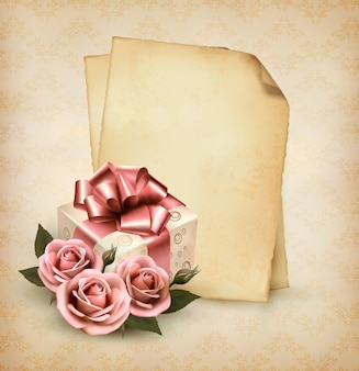 Retro holiday background with pink roses and gift box and old paper.