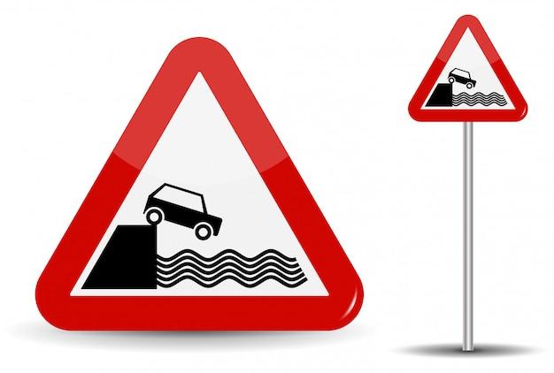 Дорожный знак предупреждение выезд на набережную. в красном треугольнике схематично изображены побережье, вода и машина.