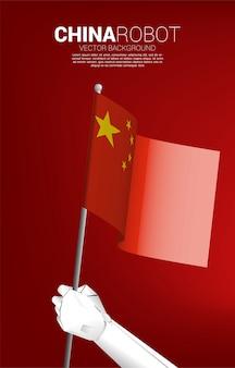 中国の旗を持つロボットの手。中国でのai学習マシン時代の概念の誕生。