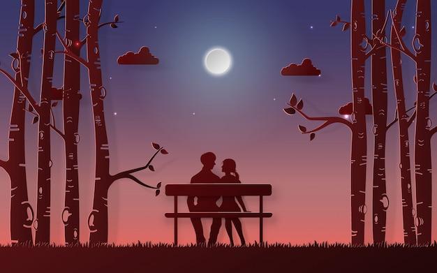 ロマンチックなカップルは月を見てベンチに座っています。
