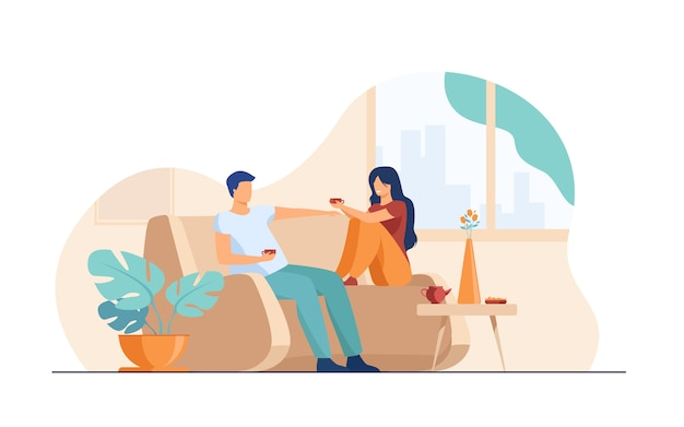 Romantic couple sitting at sofa, talking and drinking coffee