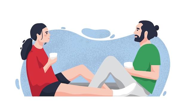 바닥에 앉아 차 또는 커피를 마시는 낭만적 인 파트너. 귀여운 남자 친구와 여자 친구가 집에서 함께 시간을 보내고.
