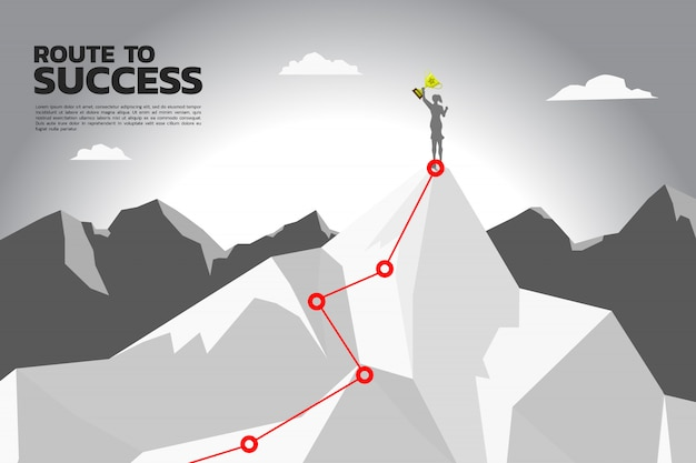 Route to success. silhouette of businesswoman with champion trophy on the top of mountain.
