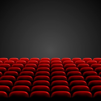 Rows of red cinema or theater seats in front of black blank screen. wide empty movie theater auditorium with red seats.