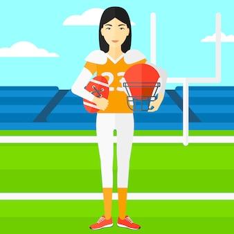 ボールとヘルメットを手に持つラグビー選手。