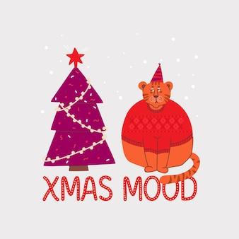 セーターを着た悲しくて不機嫌そうなトラがクリスマスツリーを見ています。クリスマスムードのレタリング。
