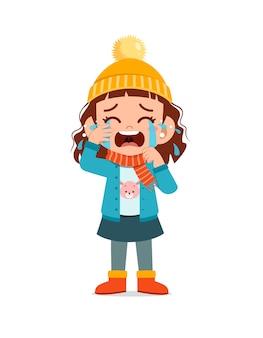 슬픈 귀여운 꼬마가 울고 겨울철 재킷을 입는다.