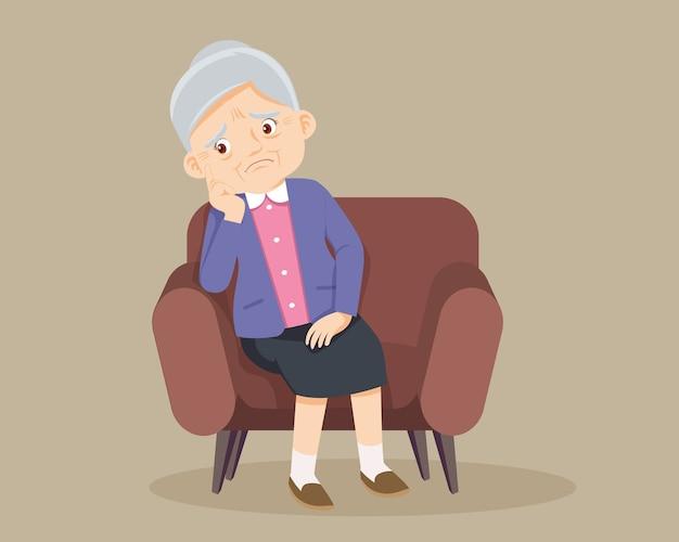 Грустная пожилая женщина скучно, старший женщина сидит в одиночестве на диване