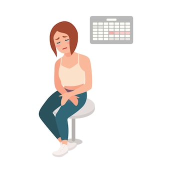 Sad girl sitting on stool with her hands on belly, suffering from menstrual pain and cramps, crying against calendar hanging on wall