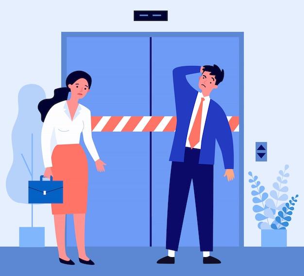 Грустный мужчина и женщина, стоящая перед сломанным лифтом