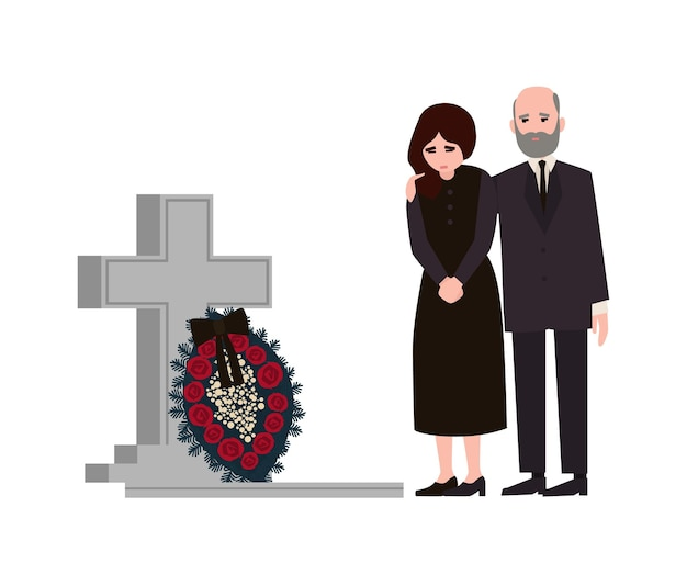 Sad man and woman dressed in mourning clothes standing near grave with tombstone and wreath