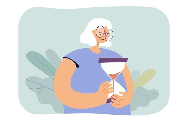 Sad old woman holding hourglass