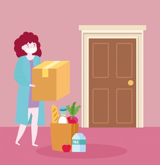 コロナウイルスcovid-19中に自宅で安全な配達、マスクの食料品の袋の食品と箱を持つ若い女性