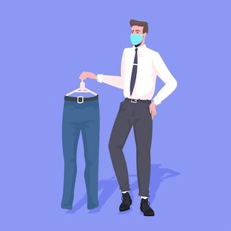 Продавец в маске показывает одежду концепции карантина пандемии коронавируса