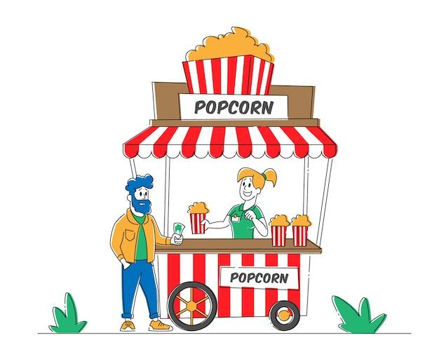 セールスウーマンは、ストリートのブースでポップコーンを若い男性の顧客に販売します