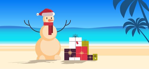 砂浜のクリスマス雪だるまギフトプレゼントボックス幸せな新年休暇休日のお祝いのコンセプト熱帯のビーチの海景の背景全長フラット