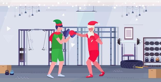 엘프 도우미 운동 건강한 라이프 스타일 크리스마스 휴일 축하 개념 현대 체육관 인테리어와 권투 연습을 연습 산타 클로스 복서