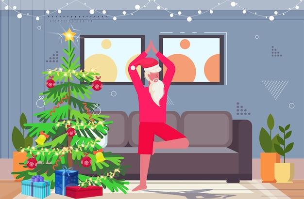 요가 연습을 하 고 산타 클로스 수염 난된 남자 트리 위치 훈련 운동 개념에 서 크리스마스 새해 휴일 현대 거실 인테리어