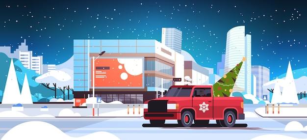 モミの木と赤いピックアップ車を運転するサンタクロースメリークリスマス冬の休日のお祝いのコンセプト現代の街の通り雪の街並み水平フラットベクトル図
