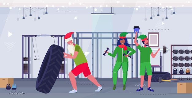 Santa claus flipping tire elves exercising with dumbbells and kettlebell training workout healthy lifestyle concept christmas new year holidays modern gym interior