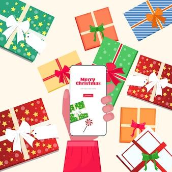 オンラインモバイルアプリを使用してサンタクロースの手メリークリスマス新年あけましておめでとうございます冬休みお祝いコンセプトスマートフォン画面